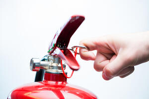 Hand pulling pin of fire extinguisher